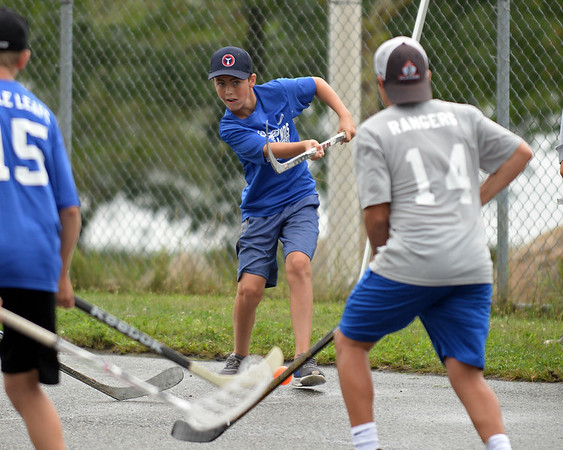 RYAN HUTTON/ Staff photo<br /> The Maple Leafs' Brett Cunningham fires a shot past the Rangers' Jack Costanzo during the Young Legends Youth Street Hockey League's finals at the Stage Fort Park basketball courts on Sunday.