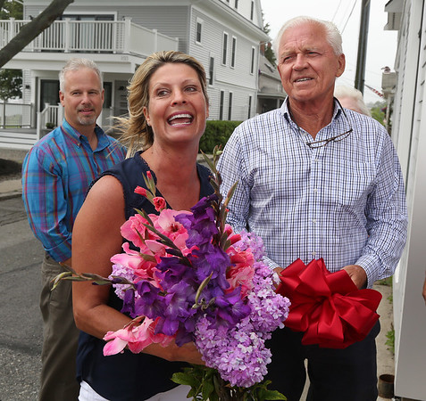 MIKE SPRINGER/Staff photo Susan Kelly speaks at the grand opening ceremony for the new location of Microsearch as her husband and business partner Chuck, right, looks on Wednesday at 101 Western Avenue in Gloucester. In the background at left is Ken Riehl, chief executive officer of the Cape Ann Chamber of Commerce. 8/2/2018
