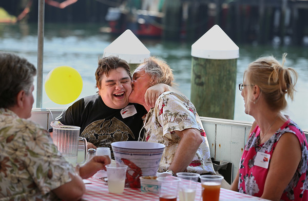 MIKE SPRINGER/Staff photo<br /> Jay Powers gives fellow adult foster care client Nicole Andersen a kiss during Adult Foster Care of the North Shore's annual summer lobster party Monday at the Seven Seas Wharf at Gloucester House.<br /> 8/6/2018