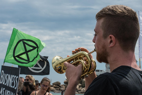 Desi Smith Photo/Gloucester Daily Times.   Scott Gilman of Somerville, plays taps during a rally at Good Harbor Beach Sunday afternoon.  Aug 4,2019
