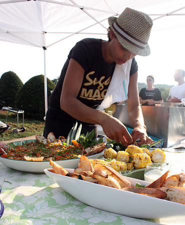 MARIA UMINSKI/Gloucester Daily Times. Linda Sands of Sugar Magnolia's plates her dish during the fourth-annual Cape Ann Farmer's Market Seafood Throwdown. The both teams had to incorporate Ocean Perch into their dishes, which was the mystery ingredient.