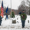 SAM GORESH/Staff photo. Gloucester High School sophomore and member of the US Naval Sea Cadet Corps, Eliabeth Schuster, salutes a wreath representing the Navy during the ceremony of Cape Ann's Wreaths Across America at Beech Grove Cemetery in Rockport as Ryan Field and Kajsa Curcuru, also with the US Naval Sea Cadet Corps hold flags behind her. 12/17/16