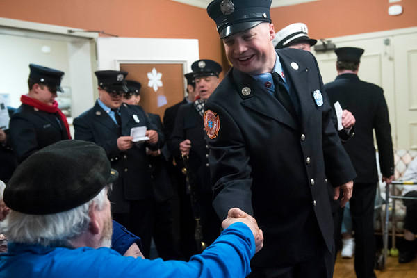 SAM GORESH/Staff photo. Firefighter and paramedic Doug Sherman shakes Golden Living Center resident Ernest Rose's hand while singing Christmas carols with other firefighters and paramedics at the Golden Living Center. 12/22/16