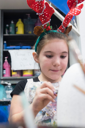 SAM GORESH/Staff photo. Isabella McLaughlin, 9, paints  a buoy for the lobster pot tree at the Cape Ann Art Haven, during the Middle Street Walk. 12/10/16
