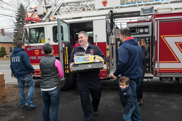SAM GORESH/Staff photo. Fire chief Eric Smith helps unload toys from the ladder truck to the Wellspring House as part of their annual toy drive. The Wellspring House offers families in need the chance to shop for toys donated by locals. For the past four years firefighter Dean DeCoste has helped fundraise and shop for toys. He said that between a GoFundMe page and firefighters collecting donations outside of  Stop and Shop they raised over $3,000 and used it to get gifts for teens which the Wellspring House said they needed. 12/8/16