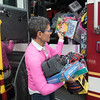 SAM GORESH/Staff photo. Laura Pedone, adult education coordinator at the Wellspring House, helps unload toys that firefighters brought as part of their annual toy drive. The Wellspring House offers families in need the chance to shop for toys donated by locals. For the past four years firefighter Dean DeCoste has helped fundraise and shop for toys. He said that between a GoFundMe page and firefighters collecting donations outside of  Stop and Shop they raised over $3,000. 12/8/16