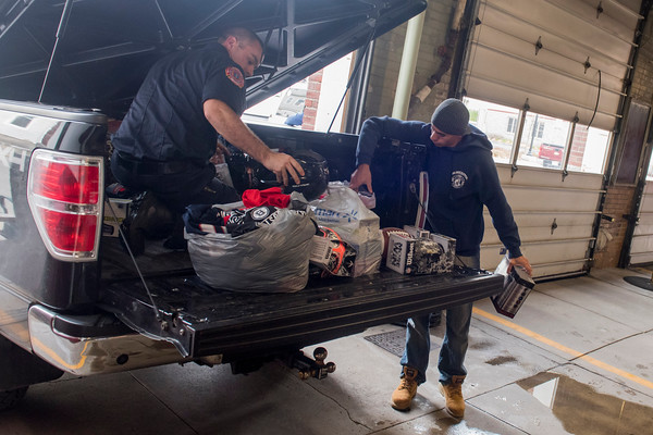 SAM GORESH/Staff photo. Firefighters David Barrett (left) and Wellington Machado help unload toys from firefighter Dean DeCoste's truck that they will deliver to the Wellspring House on their ladder truck. The Wellspring House offers families in need the chance to shop for toys donated by locals. For the past four years firefighter Dean DeCoste has helped fundraise and shop for toys. He said that between a GoFundMe page and firefighters collecting donations outside of  Stop and Shop they raised over $3,000 and used it to get gifts for teens which the Wellspring House said they needed. DeCoste said that some of the teenage employees at Walmart helped them pick out the gifts. 12/8/16