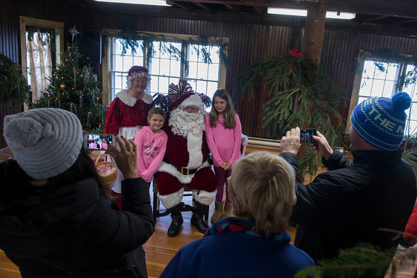 SAM GORESH/Staff photo. Jillian, 7, (left) and her sister Sophia Fialkosky, 8, (right) pose for photos with Santa and Mrs. Claus at the Old Firehouse during Rockport's Christmas celebration. 12/3/16