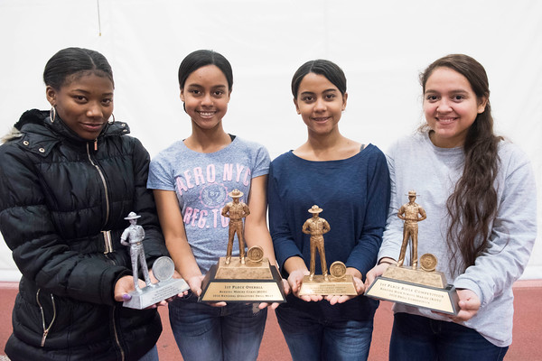 SAM GORESH/Staff photo. From left: sophomore Tyla Ordonez, junior Ruth Zorilla, senior Raysa Zorilla and senior Mayra Oliveira, members of Gloucester High School's JRROTC drill team pose for a portrait with their trophies after winning the unarmed events in the Northeast Regional championships and earning a spot in the JROTC nationals in April in Irving Texas. 12/13/16