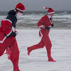 SAM GORESH/Staff photo. run through the rain and wind down Good Harbor Beach during the Seaside Santa race. 12/17/16