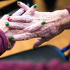 SAM GORESH/Staff photo. A resident at the Golden Living Center wears a holiday themed manicure as she listens to firefighters and paramedics sing Christmas carols. 12/22/16