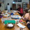 SAM GORESH/Staff photo. From left: Rose Warner, 8, Naoni Chapma, Carla Symond, Libby Mulry, 11, and Eddie Mulry, 12, make Christmas cards for veterans at the T.O.H.P. Burnham Library. 12/5/16