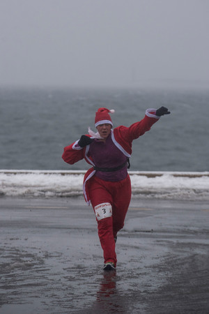 SAM GORESH/Staff photo. Osha Saylor  of Gloucester cheers as she reaches the finish line at the Seaside Santa race. 12/17/16
