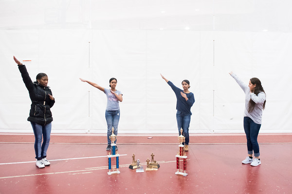 SAM GORESH/Staff photo. From left: sophomore Tyla Ordonez, junior Ruth Zorilla, senior Raysa Zorilla and senior Mayra Oliveira, members of Gloucester High School's JRROTC drill team demonstrate part of their routine as they pose for a portrait with their trophies after winning the unarmed events in the Northeast Regional championships and earning a spot in the JROTC nationals in April in Irving Texas. 12/13/16