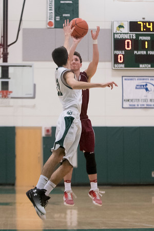 SAM GORESH/Staff photo. Rockport junior Nicholas Rodriguez shoots the ball as Manchester-Essex senior Jacob Callahan attempts to block him in their game at Manchester-Essex. 12/23/16