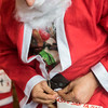 SAM GORESH/Staff photo. Mark Corgan pins his bib number onto his Santa suit before the Seaside Santa race. 12/17/16