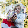 SAM GORESH/Staff photo. Frankie Sullivan, 2, takes stock of the goodie bag she received from Santa as she sits on her father Troy Sullivan's shoulders in Rockport's Dock Square. 12/25/16