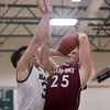SAM GORESH/Staff photo. Rockport senior Daniel Ryan shoots the ball as Manchester-Essex senior Marco Kaper attempts to block him in their game at Manchester-Essex. 12/23/16