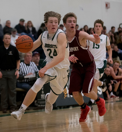 SAM GORESH/Staff photo. Manchester-Essex junior Lake Flemming races down the court with the ball as Rockport junior Quinn Murdock chases him in their game at Manchester-Essex. 12/23/16