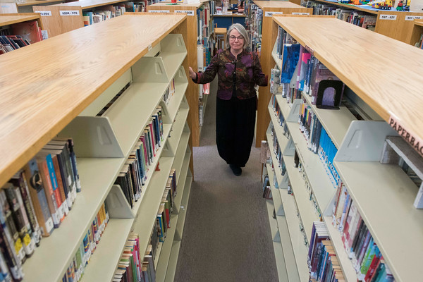 SAM GORESH/Staff photo. Sawyer Free Library executive director Deborah Kelsey poses for a portrait in the bookshelves of the children's area which she says will be modernized in a new building project which they are applying for a grant to help fund, but will also require community support. 12/5/16