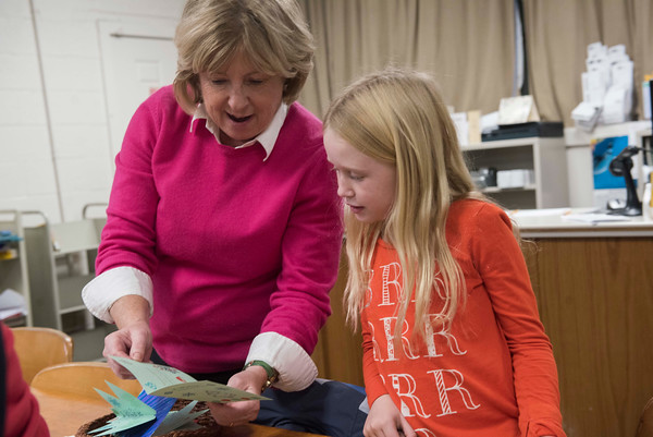 SAM GORESH/Staff photo. Library director Debbie French (left) admires a Christmas card that Laila Mears, 8, (left) made during an activity for library patrons to make Christmas cards for veterans at the T.O.H.P. Burnham Library. 12/5/16