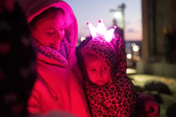 SAM GORESH/Staff photo.Serena Hopkinson holds her daughter Jasmine Delssabtos, 1, at the Lobster Pot Christmas Tree Lighting in Police Station Plaza. 12/10/16