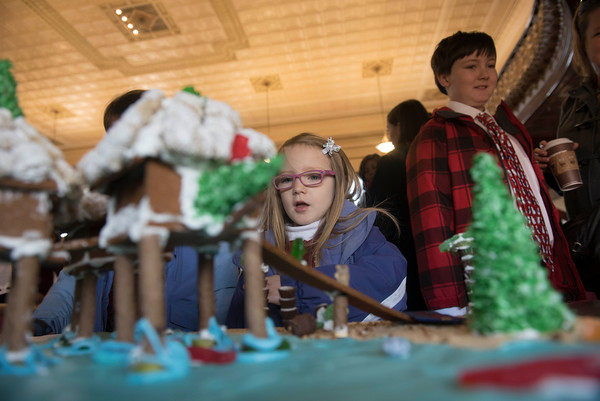 SAM GORESH/Staff photo. Isabel Porter, 4, amores a gingerbread house at City Hall's Kyrouz Auditoriumduring the Middle Street Walk. 12/10/16