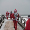 SAM GORESH/Staff photo. Runners run across the bridge to the road from Good Harbor Beach in the Seaside Santa race. 12/17/16