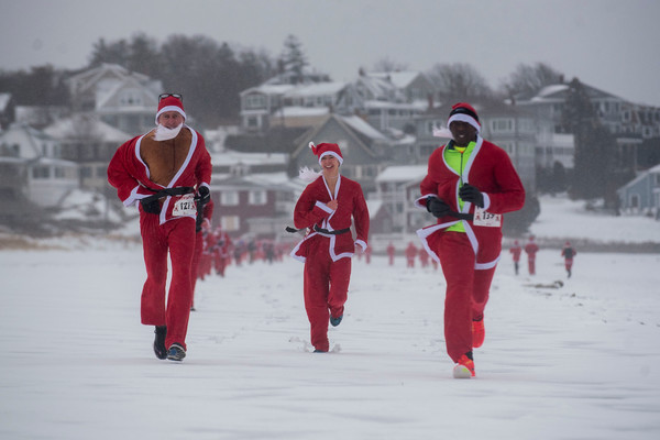 SAM GORESH/Staff photo. From left: Scott Levasseur Annelise Eaton,  andDavid Ndungu lead the way down Good Harbor Beach through the rain in the Seaside Santa three mile race. The three runners took fourth, first and second place with Eaton beating Ndungu by one second. 12/17/16