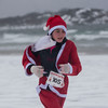 SAM GORESH/Staff photo. Mollie Lytje age 12 runs down Good Harbor Beach in the Seaside Santa race. 12/17/16