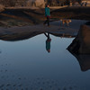 SAM GORESH/Staff photo. Tara Lake is reflected in a tide pool during low tide with her dog Lily and mother-in-law Mary Beth Lake at Wingaersheek Beach. 12/23/16