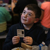 MIKE SPRINGER/Staff photo<br /> Second-grader Ryder Raynes holds a police officer trading card after it was given to him by a Gloucester policeman during lunch Tuesday at Plum Cove Elementary School.<br /> 12/07/2017