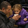MIKE SPRINGER/Staff photo   <br /> Carlos DeJesus of Gloucester helps his daughter Nora, 2, drink a cup of hot chocolate at Art Haven while they wait for the annual lobster trap Christmas tree lighting ceremony Saturday at Police Station Plaza in downtown Gloucester.<br /> 12/09/2017