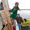 "Elf Samantha Lucas climbs down a ladder at Granite Pier to board the Lobster boat ""William G. Drohan"" to help transport Santa to T-Wharf at Rockport Harbor for the annual parade and tree lighting on Saturday December 2, 2017 in Rockport, Ma.  Joseph Prezioso/Photo"