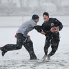 MIKE SPRINGER/Staff photo   <br /> Navy ball-carrier Haran Ellis, an active U.S. Coast Guard member, tries to break away from an Army defender during the first-ever Army-Navy flag football game for veterans Saturday at Newell Stadium in Gloucester<br /> 12/08/2017