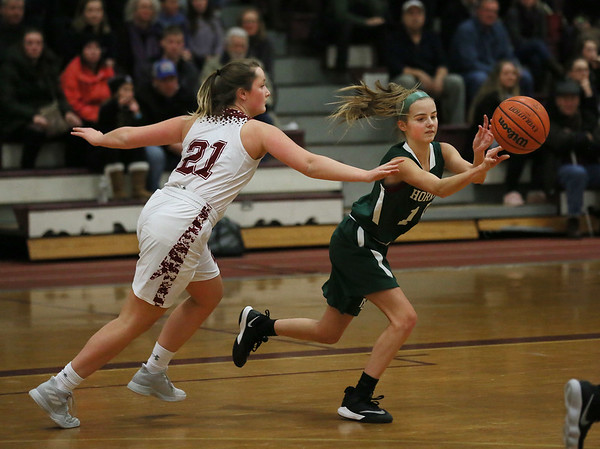 MIKE SPRINGER/Staff photo   <br /> Suzy Morton, right, of Manchester Essex passes the ball away from Gloucester's Claire Knowlton during varsity basketball action Thursday in Gloucester.<br /> 12/28/2017