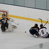MIKE SPRINGER/Staff photo<br /> Goalie Justin Miner of Minuteman deflects the puck away from the net as Rockport's Nick Fonzi, right, slides away from the net after the play was broken up by Minuteman defenseman Chris Leary during varsity hockey action Wednesday in Gloucester.<br /> 12/27/2017