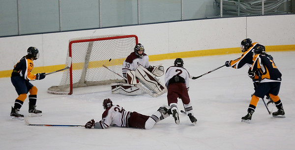MIKE SPRINGER/Staff photo<br /> Rockport's Will Zambernardi sprawls on the ice as a shot from Stephen Vozzella of Minuteman slips past Rockport goalile Cal Twombly in the first period of varsity hockey action Wednesday in Gloucester.<br /> 12/27/2017