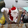 Santa climbs up a ladder from the lobster boat and onto T-Wharf at Rockport Harbor for the annual parade and tree lighting on Saturday December 2, 2017 in Rockport, Ma.  Joseph Prezioso/Photo