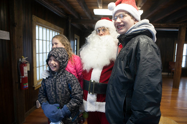 AMY SWEENEY/Staff photo. Caitlin, Nathan and Patrick Morin pose for a photo with Santa during his visit on Christmas morning to Rockport. <br /> 12/25/17