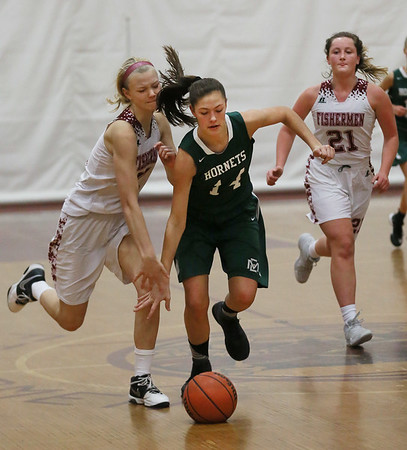 MIKE SPRINGER/Staff photo   <br /> Bridget Twombly, center, of Manchester Essex keeps the ball away from Gloucester's Beatrice Sumner, left, and Claire Knowlton during varsity basketball action Thursday in Gloucester.<br /> 12/28/2017