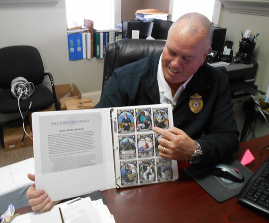 "SEAN HORGAN/Staff photo/Essex police Chief Peter G. Silva laughs while pointing to the collectible card for his secretary, Mary Elinor Dagle, part of the department's rejuventated collectible card program. He called Dagle's card ""the wild card."""