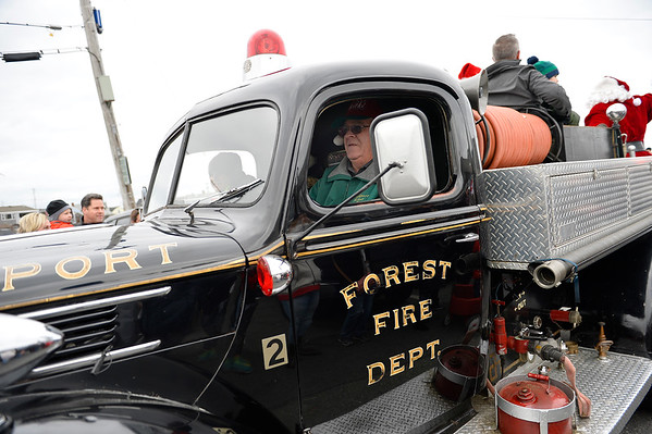 Jerry Beckham drives the old Forrest Fire Dept. fire truck in the annual parade that lead Santa to the Old Firehouse on Pleasant St. before the annual tree lighting on Saturday December 2, 2017 in Rockport, Ma following Santa's arrival via lobster boat on T-Wharf.  Joseph Prezioso/Photo