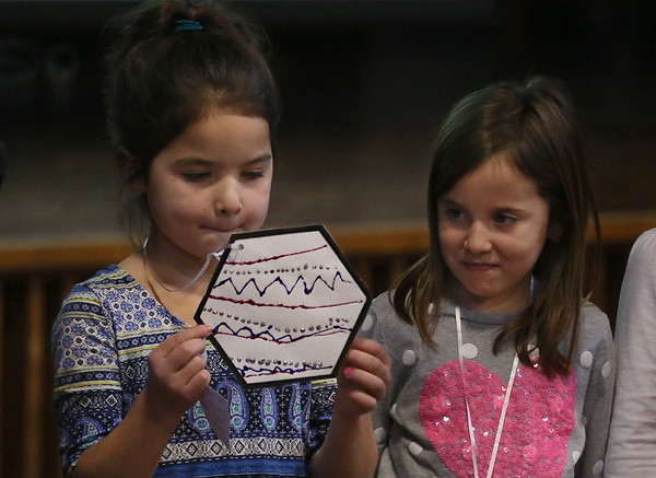 "MIKE SPRINGER/Staff photo   <br /> First-grader Emma Brown, left, presents a hexagon -- a six-sided polygon -- as her classmate Sarina Racofsky looks on Wednesday during a  ""Polygon Parade"" Wednesday at Beeman Elementary School.<br /> 12/20/2017"