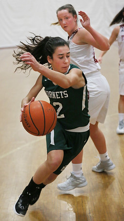 MIKE SPRINGER/Staff photo   <br /> Lily Athanas of Manchester Essex drives the ball past Claire Knowlton of Gloucester during varsity basketball action Thursday in Gloucester.<br /> 12/28/2017