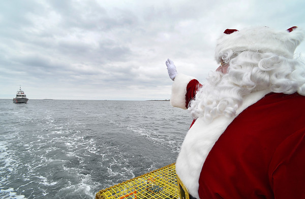 "Santa waves to a Coast Guard escort boat while on board the Lobster boat ""William G. Drohan"" on his way to T-Wharf at Rockport Harbor for the annual parade and tree lighting on Saturday December 2, 2017 in Rockport, Ma.  Joseph Prezioso/Photo"