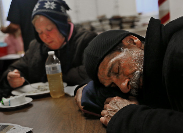 """MIKE SPRINGER/Staff photo   <br /> Tom Burgess, who lives in a hut in a forest outside of town, takes a nap after having a hot meal as Kathy Atkinson, also homeless, eats her lunch Tuesday at the Grace Center day shelter in the basement of the Unitarian Universalist Church in Gloucester. A cold rain was falling at the time the photo was taken. """"It's a place to go to get out of the weather and get something to eat,"""" Burgess said of the Grace Center. Without it, he said, """"Everybody in here would be out on the street somewhere hiding on a stoop.""""<br /> 12/12/2017"""