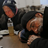 "MIKE SPRINGER/Staff photo   <br /> Tom Burgess, who lives in a hut in a forest outside of town, takes a nap after having a hot meal as Kathy Atkinson, also homeless, eats her lunch Tuesday at the Grace Center day shelter in the basement of the Unitarian Universalist Church in Gloucester. A cold rain was falling at the time the photo was taken. ""It's a place to go to get out of the weather and get something to eat,"" Burgess said of the Grace Center. Without it, he said, ""Everybody in here would be out on the street somewhere hiding on a stoop.""<br /> 12/12/2017"