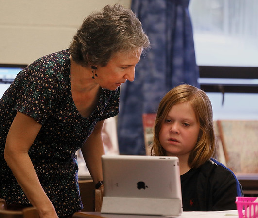 MIKE SPRINGER/Staff photo<br /> Librarian Sue Hardy helps Satchel Rubin work on a computer at Essex Elementary School.<br /> 10/23/2017