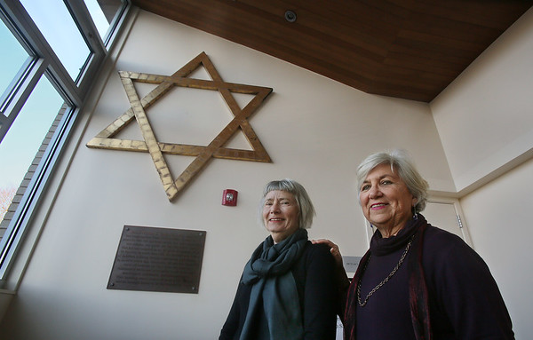 MIKE SPRINGER/Staff photo   <br /> Miriam Weinstein, left, and Carole Sharoff near the Star of David that survived the December, 2007 fire. The wooden star, which was above the entrance to the old temple, is now displayed on an upstairs wall in the rebuilt temple.<br /> 12/13/2017